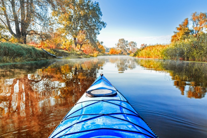 View from the blue kayak on the river banks with autumnal yellow leaves trees in fall season. The Seversky Donets river, autumn kayaking. View over nose of bright yellow kayak.